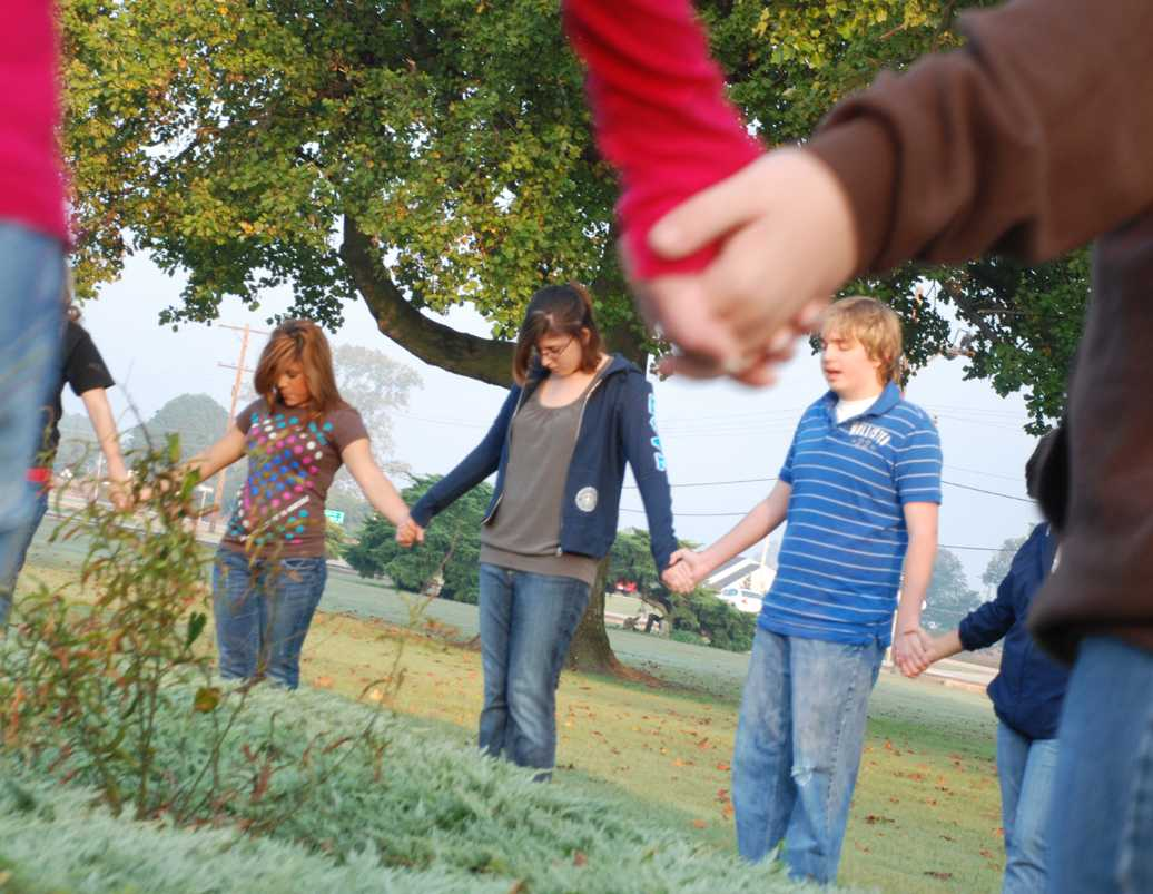 Students grasp hands in prayer at the See You at the Pole service on Wednesday, Sept. 24