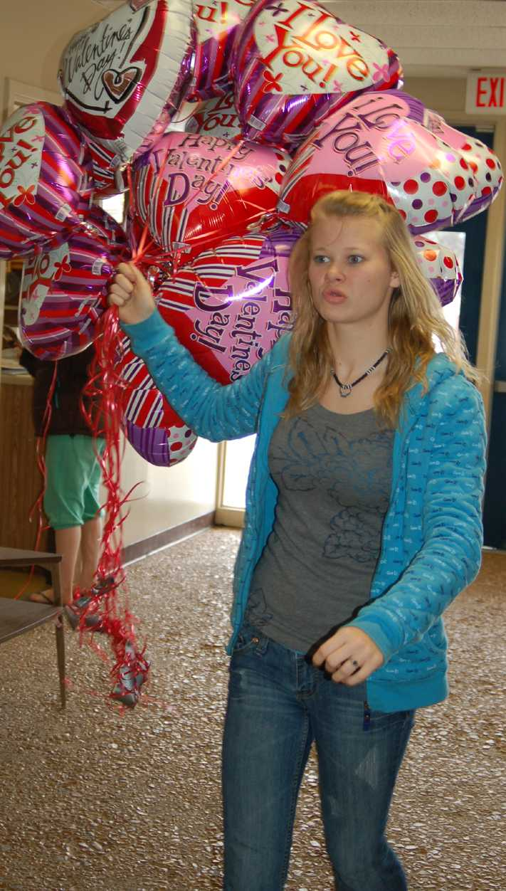 Holly Dempsey delivers Valentine balloons to the junior high. Balloon sales are a traditional fundraiser for the junior class.