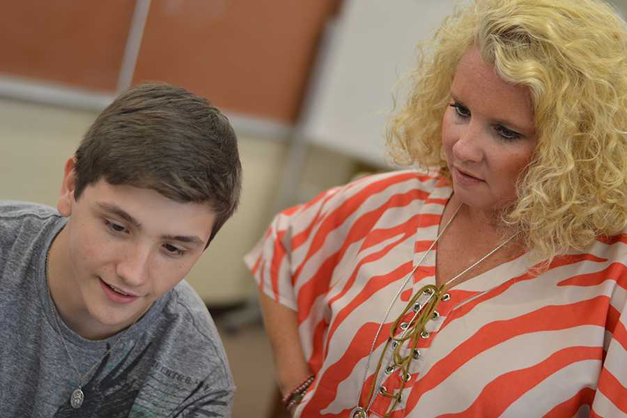 Business teacher Wendy Stewart works with senior Tyler Parker during CBA class.