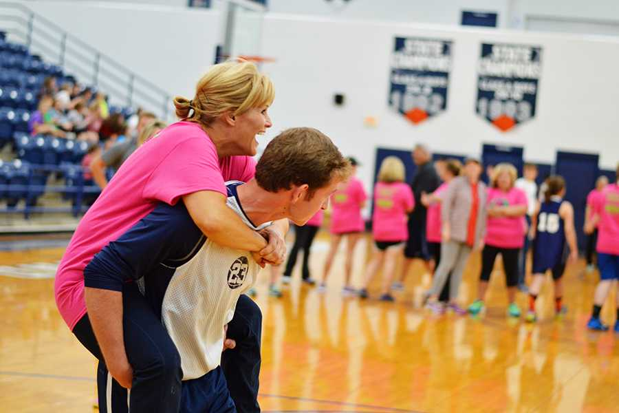 Kindergarten teacher and basketball mom April Finch gets assistance from sophomore Andrew McFarlin during the Hoops 'N Heels event Tuesday night at the MAC.