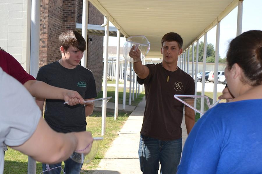 Students in Mandy McFall's science classes recently did outdoor experiments with handmade bubble wands and solution. McFall's 2015 biology students have recently been recognized for their performance on the EOC. Pictured are, from left, Chase Ellis, Hunter Drury and Hannah Harrell.