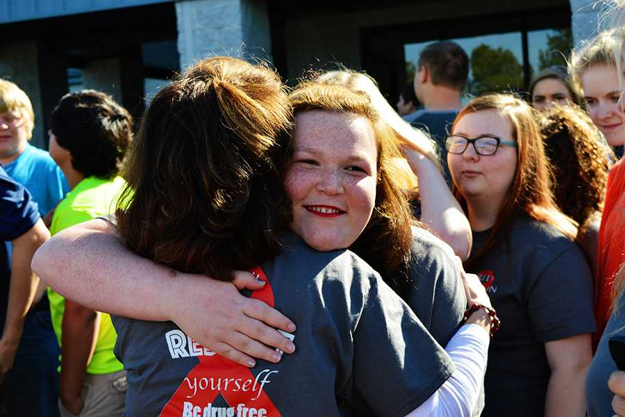 Senior Maria Hart embraces EAST instructor Jill Sanders after the balloon release. Hart was one of the organizers of the event and spoke candidly about her family's struggles with addiction.