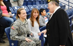 Seniors Natalie Campbell and Jessica Krob talk with Navy veteran Marie George before Monday's assembly.