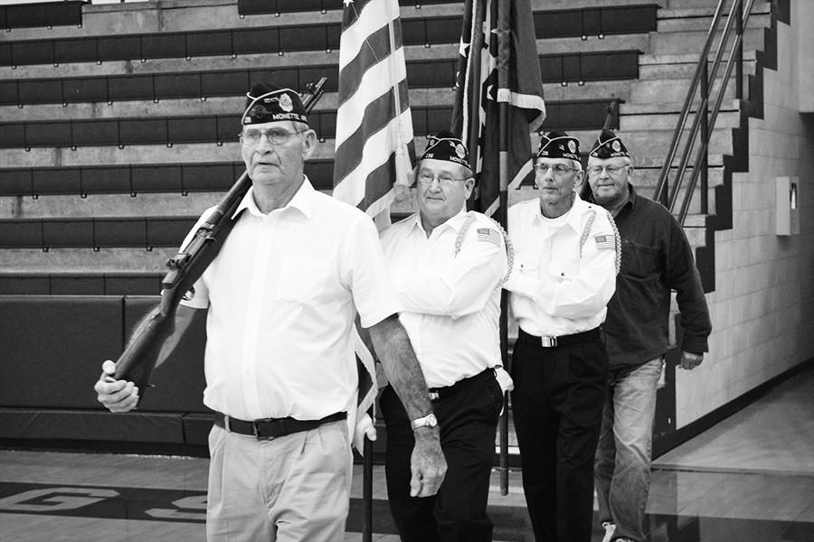 Larry Rolland (front) of Monette leads the color guard at the start of Monday's Veterans Day assembly in the MAC.