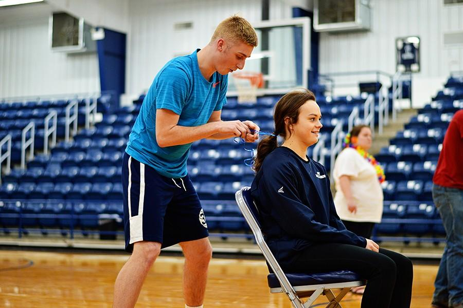 Chayse Carmichael had great difficult tying a ribbon in Heather Sipes's hair during the Let's Go Out event at Wacky Olympics.