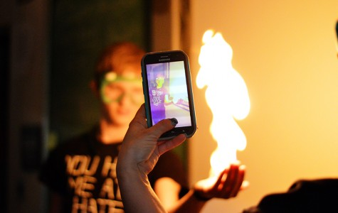 Teacher Stephanie Woods films Junior J.J. Ivy holding a flame during an experiment in class. Each student enrolled in chemistry had the opportunity to try this experiment.