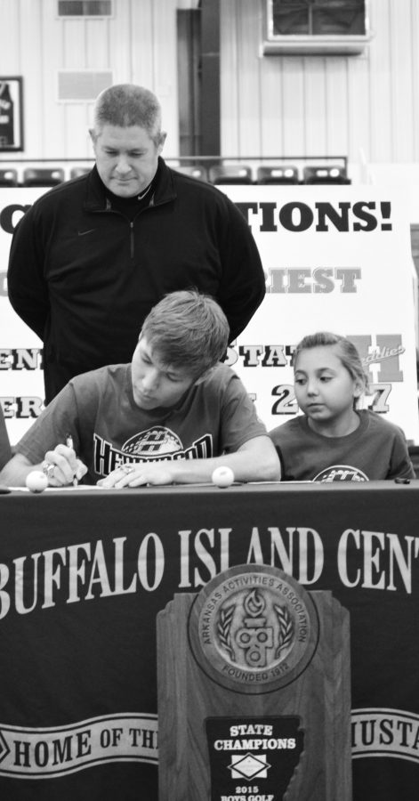 Trey+signs+a+commitment+to+play+golf+at+Henderson+State+University+while+Coach+Yates+and+his+younger+sister+look+on.+